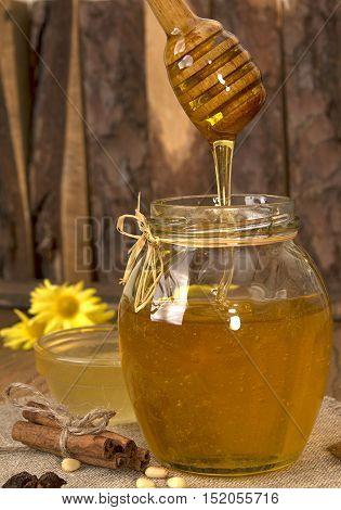 Delisious Sweet Honey Flowing Down In Glass Jar.