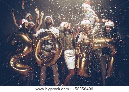 Happy New 2017 Year! Group of cheerful young people in Santa hats carrying gold colored numbers and throwing confetti
