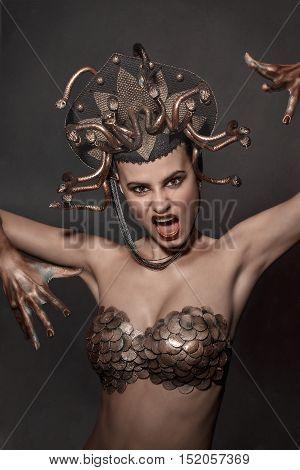 girl Medusa headdress of gold color on a black background.