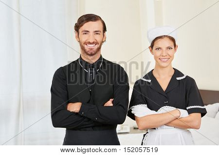 Concierge and maid in uniform in hotel room as service team