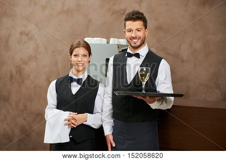 Waiter and waitress serving white wine in a hotel restaurant