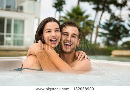 Young couple in a luxury hotel embraced inside a jacuzzi and enjoying the holidays