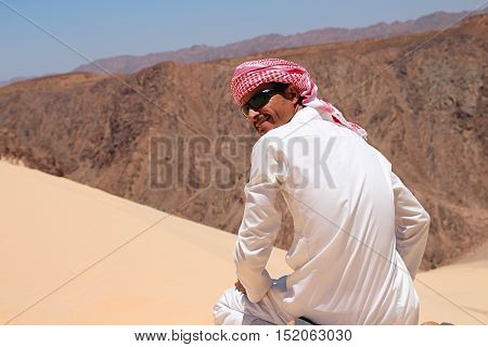 Man in bedouin clothes sitting on dune