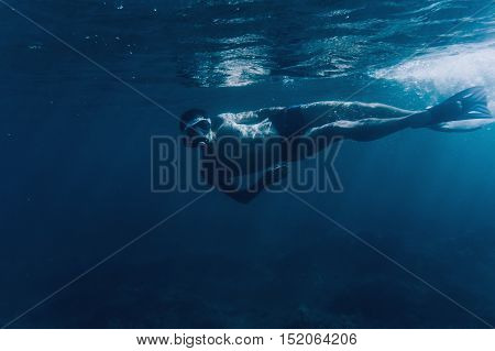 Young man free diver swimming underwater in blue deep sea looking at camera