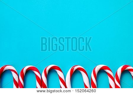 Striped candy canes as walking sticks on the blue surface