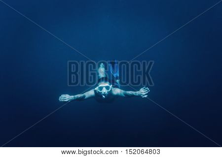 Sporty young man free diver swimming underwater in blue deep sea looking at camera