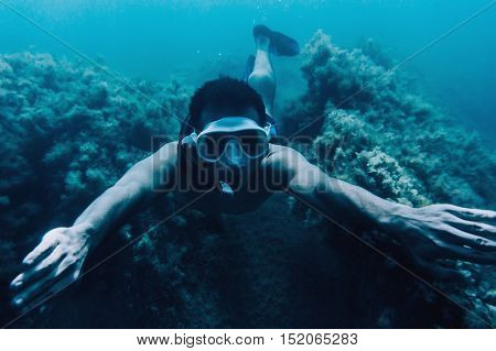 Underwater image of young man free diver swimming among seaweed