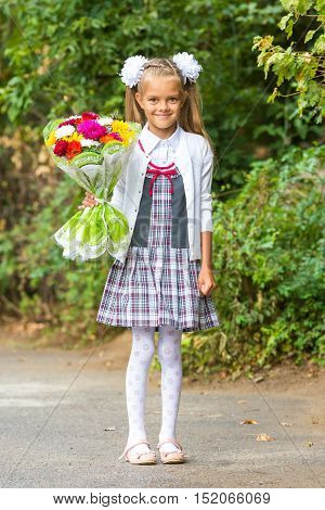 Portrait Of A Seven-year First-grade Girl With A Bouquet Of Flowers