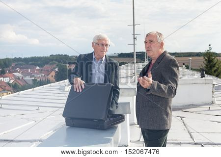 Two senior businessmen with briefcase discussing business deal outdoors on the roof of a building.
