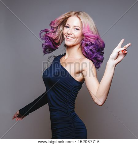 Dancing women with colored hair. Smiling. Showing peace. Ombre. Studio