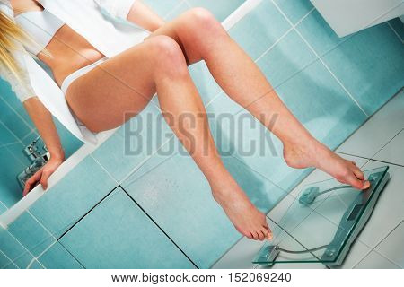 closeup on very attractive girl weighing in bathroom