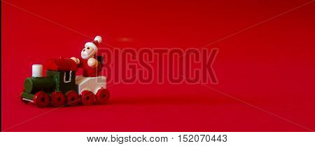 Typical German Wooden Decoration For Christmas Time Of A Man Upon A Train With Copyspace. Red Backgr