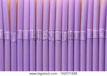 Drink tube of violet color in abstract background for the design idea backdrop.