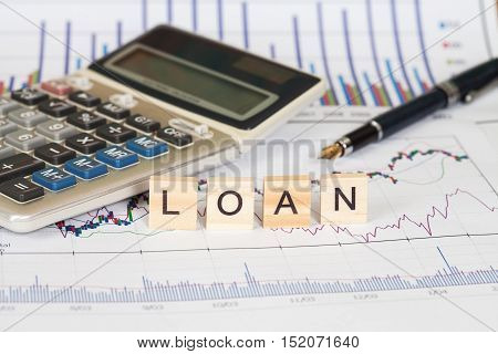 Calculator and business data with the word loan written in wooden block