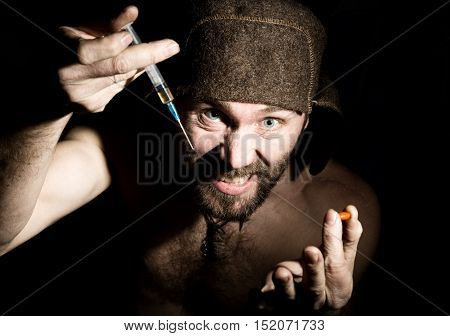Dark portrait of scary evil sinister bearded man with smirk, offers a variety of drugs, a syringe or a pill. strange Russian man with a naked torso and a woolen hat.