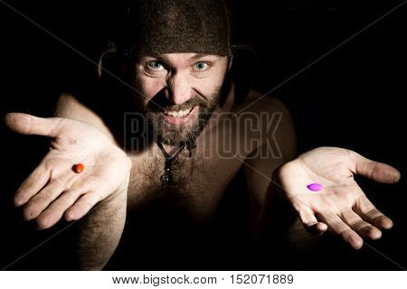 Dark portrait of scary evil sinister bearded man with smirk, offers a choice of orange or purple pill. strange Russian man with a naked torso and a woolen hat.