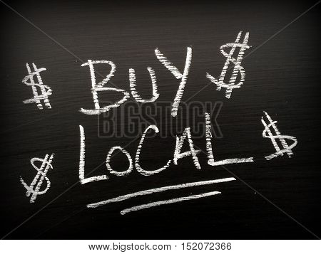 The words Buy Local written in white chalk on a blackboard with dollar signs as a reminder to support your local business