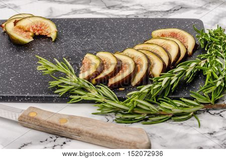 Fresh sliced figs rosemary and knife on cutting board