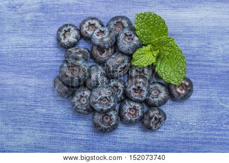Fresh blueberries with mint leaf on rustic textured background with copy space