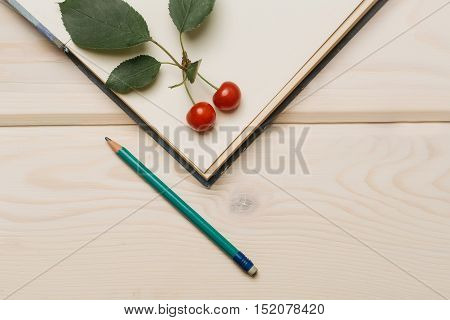 Two ripe red cherries with green leaves on open paper diary and graphite pencil on light wooden background copy space