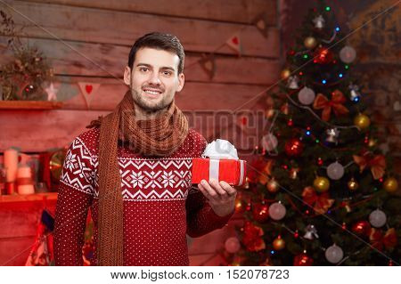 Portrait of happy man in holding giftbox. Handsome smiling male wearing warm sweater with red gift box in hands over christmas tree.