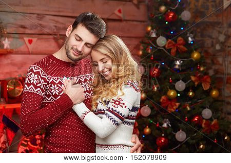 Happy couple in love over christmas tree. Young smiling couple of man and blond woman wearing sweaters dreaming with eyes closed. Make a wish on christmas night