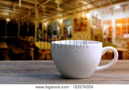 White Coffee cup on wooden table in coffee shop blur backgroundvintage style effect picture.