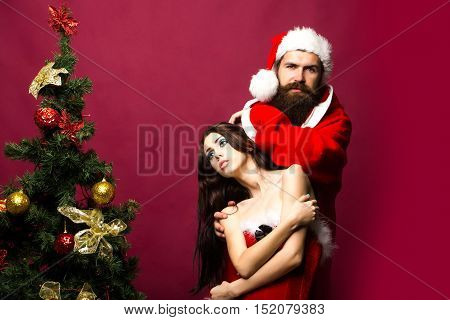 bearded santa claus man with long beard in new year coat and hat with pretty sexy girl or woman near decorated Christmas tree on pink background