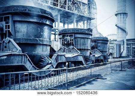 Steelworks landscape train loaded with huge cans.
