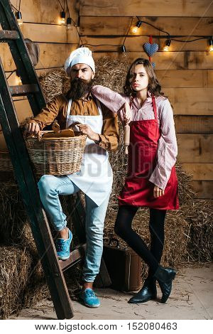 Handsome man chef cook or baker with beard and moustache in hat toque with cute girl cookee teenager in apron stand at wooden ladder with basket on rustic background
