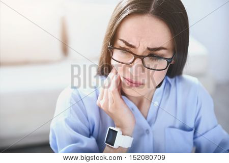 Something with my teeth. Pretty young woman touching jowl and having toothache while sitting by the table