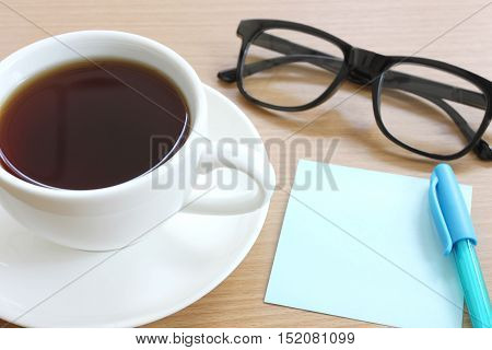 Paper note on the wooden work table you can input text to copy space in Business concept.