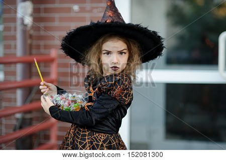 The girl of 8-9 years is dressed in a suit of the angry sorcerer. On her face the corresponding make-up. In hands at the little girl a magic wand and a vase with candies. Halloween.