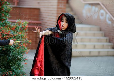 Boy of younger school age in a black-red cloak portrays the evil sorcerer. Boy has a mysterious look. He does the relevant movements by hands.