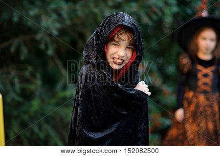 Boy of younger school age in a black-red cloak portrays the evil sorcerer. On the face of the boy corresponding make-up. Boy has a mysterious look. In the background silhouette of the girl-witch.