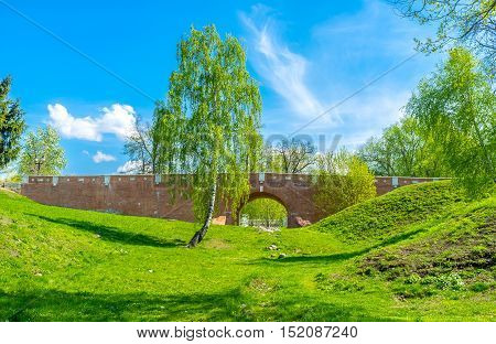 The walk along the sunny ravine with the view on Greenhouse Bridge between the Royal Greenhouses and Bread House Tsaritsyno Moscow Russia.