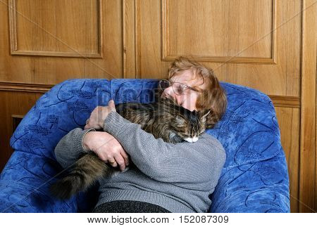 Old Woman Asleep In A Chair In An Embrace With A Cat