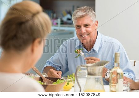 Portrait of senior man eating food while looking at wife. Healthy older man having lunch at home. Cheerful couple enjoying lunch.
