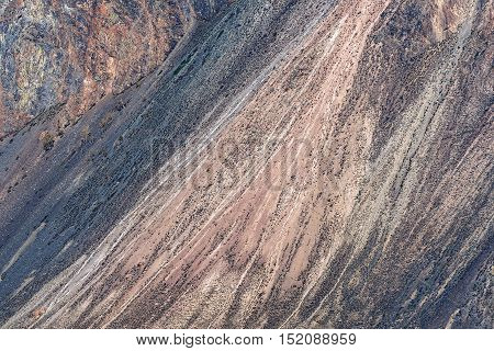 Scenic natural abstract background from texture of the mountain with stones scree and sparse vegetation