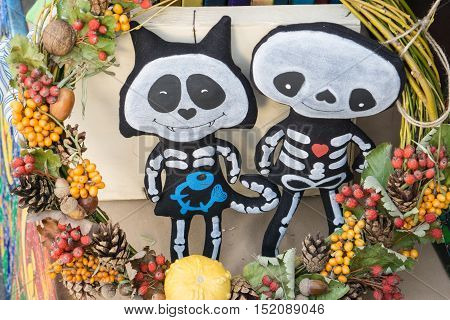very cute handmade dolls of a cat kitty with friend made for helloween with whreas circlet made of different fruits berries nuts pinecones pumpkin