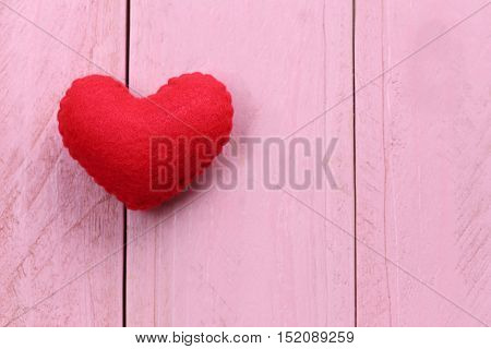 Red heart is placed on a pink wooden floor concept of love in Valentine's Day.