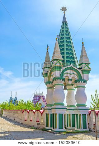 The small green tower topped with the golden star has colorful conical roof figured pillars and located at the bridge of Izmailovsky Kremlin Moscow Russia.