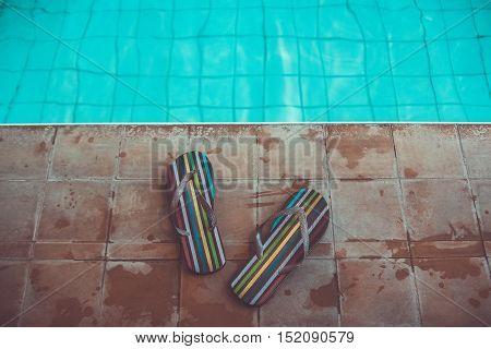 beach slippers stripped flip flops near sport pool with blue water