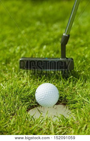 Putter Pushing a Golf Ball in a Hole