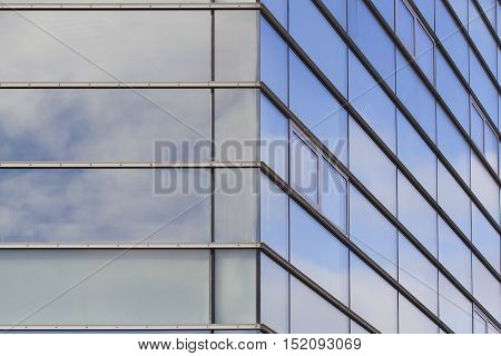 Modern office building fasade with clouds reflected in windows. Close up