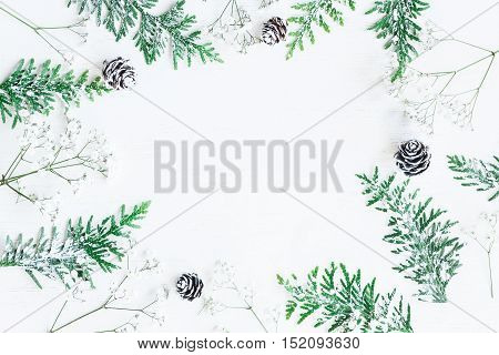 Winter frame made of pine cones thuja branches and gypsophila flowers. Winter composition. Top view flat lay