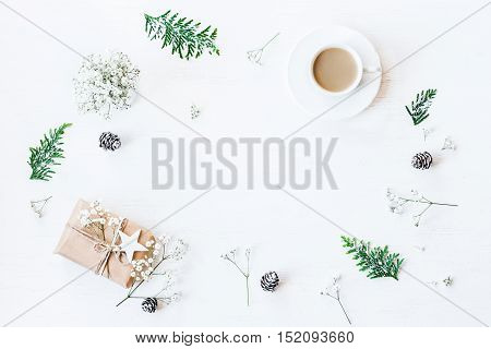 Christmas composition. Cup of coffee christmas gift pine cones thuja branches and gypsophila flowers. Top view flat lay