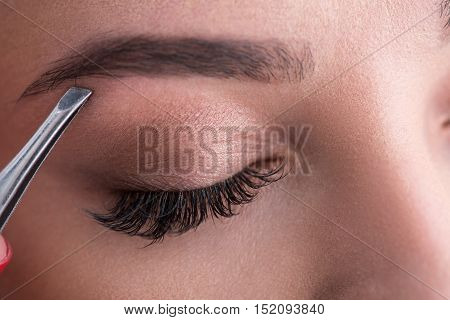My eyebrows always perfect. Closeup part of face of beautiful woman plucking eyebrows while using tweezers