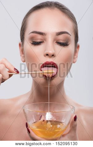 Starting day by healthy way. Cropped photo of beautiful brunette with red lips eating honey from wooden spoon and posing in studio isolated on grey background