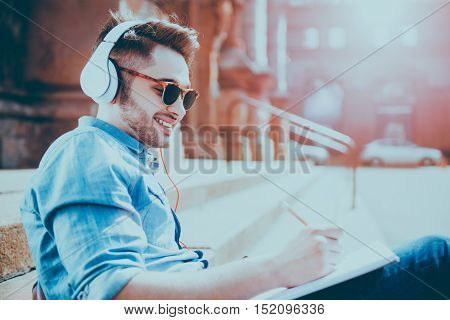 Like doing it. Positive smiling handsome guy drawing and listening to music while resting on the footsteps